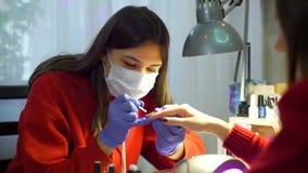 A mulher faz o tratamento de mãos para um cliente vídeos de arquivo