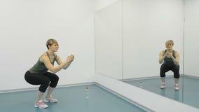 A mulher faz ocupas no gym na frente do espelho video estoque