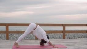 A mulher faz poses da ioga fora na natureza filme