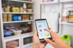 A mulher faz sua lista de compra em seu smartphone conectado ao refrigerador Fotos de Stock