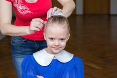 A mulher faz um penteado da menina para um desempenho Imagem de Stock