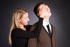 A mulher fecha as mãos atrás de um olho dos homens. Fotografia de Stock Royalty Free