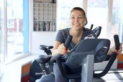 A mulher feliz é contratada em uma bicicleta estacionária fotografia de stock royalty free