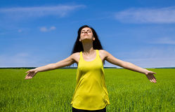 A mulher feliz aprecia o sol no campo fotos de stock royalty free