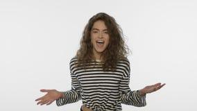 A mulher feliz aprecia a vitória no estúdio branco Retrato do salto da menina do vencedor vídeos de arquivo