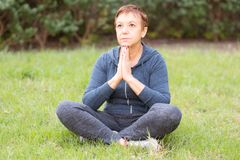 A mulher feliz ativa bonita madura na manhã no parque, relaxa após exercícios dos esportes Senhora média na pose da ioga fotos de stock royalty free