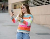 Mulher feliz atrativa do jovem adolescente que olha no vídeo esperto e nos gostos do telefone excitados e surpreendidos fotos de stock royalty free