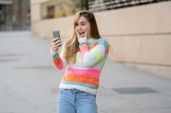 Mulher feliz atrativa do jovem adolescente que olha no v?deo esperto e nos gostos do telefone excitados e surpreendidos foto de stock
