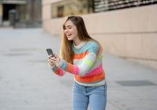 Mulher feliz atrativa do jovem adolescente que olha no v?deo esperto e nos gostos do telefone excitados e surpreendidos imagem de stock royalty free