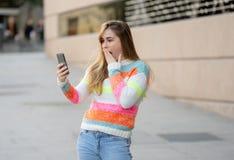 Mulher feliz atrativa do jovem adolescente que olha no v?deo esperto e nos gostos do telefone excitados e surpreendidos imagens de stock royalty free