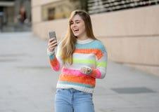 Mulher feliz atrativa do jovem adolescente que olha no v?deo esperto e nos gostos do telefone excitados e surpreendidos foto de stock royalty free