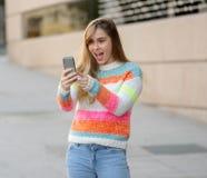 Mulher feliz atrativa do jovem adolescente que olha no v?deo esperto e nos gostos do telefone excitados e surpreendidos fotografia de stock royalty free