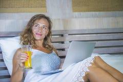 Mulher feliz atrativa e bonita nova 30s que encontra-se na cama em casa que usa o Internet que trabalha no portátil do computador foto de stock