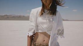 Mulher feliz atrativa na roupa ocasional leve levantamento do verão, andando para a câmera no lago quente do deserto de sal em Ut vídeos de arquivo