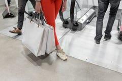 A mulher feliz bonita de Shopaholic vai comprar na cidade Moça em calças vermelhas e em muitos sacos de papel cinzentos ela fotos de stock