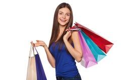 Mulher feliz bonita do sorriso que guarda sacos de compras, venda, isolada no fundo branco Foto de Stock