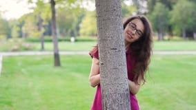 Mulher feliz bonita em um parque perto de uma árvore video estoque