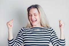 Mulher feliz bonita excitada expressando o gesto de vencimento Bem sucedido e comemorando a vitória, triunfante no fundo branco fotos de stock