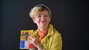 Mulher feliz bonita no revestimento amarelo que aprende a língua francesa e que sorri na câmera, isolada no fundo preto filme