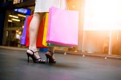Mulher feliz bonita nova de compra da mulher asiática com os sacos coloridos na alameda fotos de stock