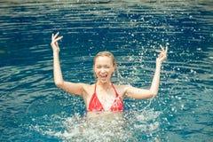 Mulher feliz bonita que espirra a água na piscina, senhora dentro fotos de stock royalty free