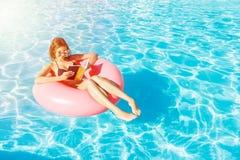 Mulher feliz bonita que lê um livro com o anel inflável que relaxa na piscina azul imagens de stock