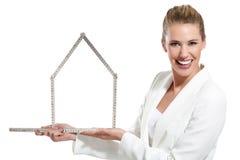 Mulher feliz bonita que mostra um símbolo da casa Foto de Stock