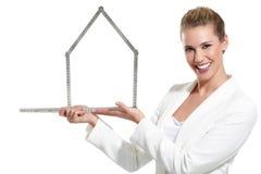 Mulher feliz bonita que mostra um símbolo da casa Fotografia de Stock Royalty Free