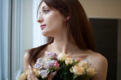 Mulher feliz bonita que olha a janela fora do quarto com um ramalhete das flores Conceito da mola fotos de stock royalty free