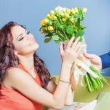 A mulher feliz bonita recebeu um ramalhete da flor das rosas Imagens de Stock Royalty Free