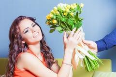 A mulher feliz bonita recebeu um ramalhete da flor das rosas Foto de Stock
