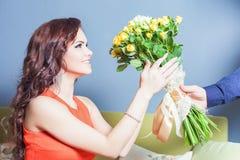 A mulher feliz bonita recebeu um ramalhete da flor das rosas Fotografia de Stock