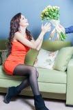 A mulher feliz bonita recebeu um ramalhete da flor das rosas Fotos de Stock Royalty Free