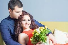 A mulher feliz bonita recebeu um ramalhete da flor das rosas Imagem de Stock