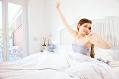 Mulher feliz bonito no hotel na manhã que estica acordar fotos de stock
