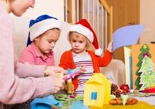 Mulher feliz com as meninas que preparam-se para o Natal Fotos de Stock Royalty Free