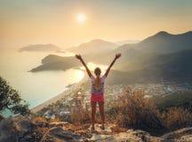 A mulher feliz com aumentado acima arma a posição na montanha Foto de Stock