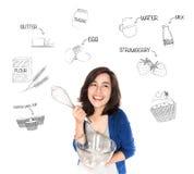A mulher feliz com batedor de ovos e a bacia de vidro que pensam do copo endurecem o recip Imagem de Stock Royalty Free