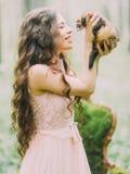A mulher feliz com cabelo encaracolado longo na luz - terra arrendada, trocas de carícias e jogo cor-de-rosa do vestido com a don foto de stock