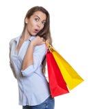 Mulher feliz com cabelo escuro e os sacos de compras longos Imagem de Stock Royalty Free