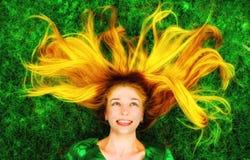 Mulher feliz com cabelo longo para baixo na grama fotos de stock royalty free