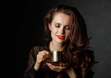 Mulher feliz com cabelo marrom e os bordos vermelhos que aprecia a xícara de café Foto de Stock