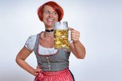 Mulher feliz com a caneca de cerveja que olha na distância Foto de Stock