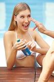 Mulher feliz com frasco da protecção solar Fotografia de Stock