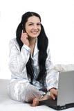 Mulher feliz com móbil do telefone e portátil na cama Imagens de Stock Royalty Free