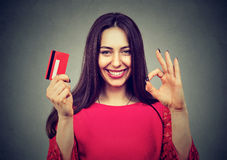 Mulher feliz com o cartão de crédito que dá o gesto aprovado do sinal da mão Imagem de Stock Royalty Free