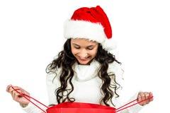 Mulher feliz com o chapéu do Natal que olha no saco de compras vermelho fotos de stock royalty free