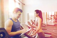 Mulher feliz com o instrutor na escada rolante no gym imagem de stock royalty free