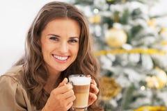 Mulher feliz com o macchiato do latte na frente da árvore de Natal foto de stock royalty free