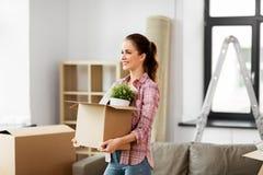 Mulher feliz com o material que move-se para a casa nova foto de stock royalty free